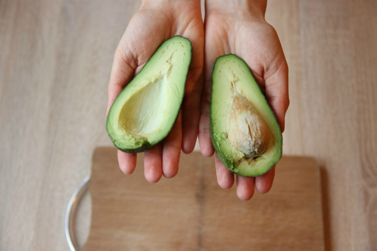 половинки авокадо в ладонях